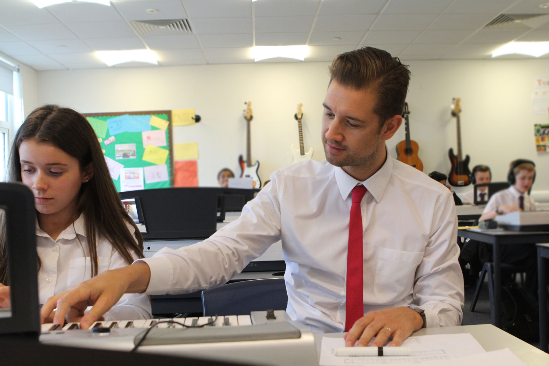 teacher and student at keyboard